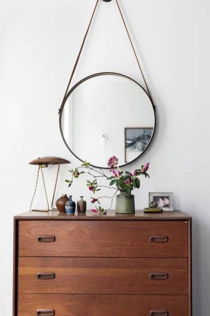 miroir-design-rond-au-dessus-de-commode-bois-foncé