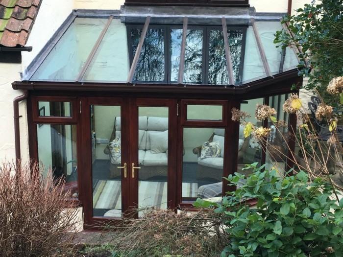 modele-de-veranda-en-aluminium-imitation-bois-veranda-toit-plat-plongé-dans-la-verdure