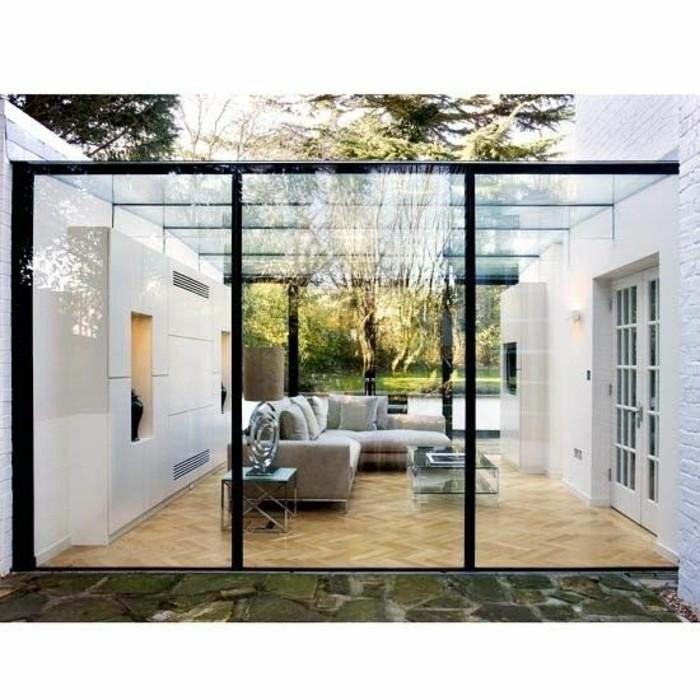 modele-de-veranda-en-verre-ultra-moderne-deco-veranda-contemporaine-canapés-gris-petite-table-basse-en-verre