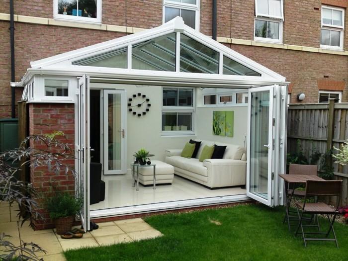 une-petite-verande-moderne-en-aluminium-une-veranda-blanche-contemporaine-contrastant-avec-la-simplisité-du-bâtiment-adjacent