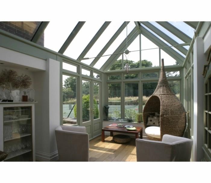 veranda-contemporaine-un-véritable-paradis-de-la-détente-deux-canapés-magnifique-balançoire-en-rotin-suspendu-toit-veranda-en-verre-table-basse
