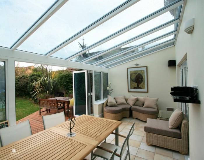 veranda-moderne-aménagé-en-magnifique-salon-meubles-en-rotin-table-en-bois-marron-atmosphère-propice-à-la-détente-toit-veranda-plat-en-verre