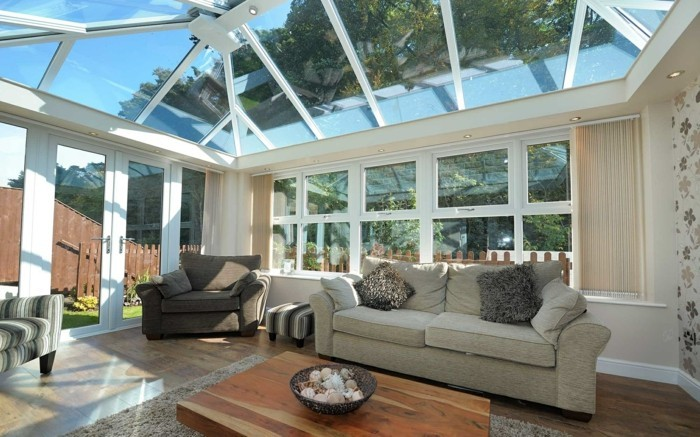 veranda-moderne-aménagé-en-salon-ambiance-accueillante-petite-table-basse-en-bois-canapé-deux-fauteuils-lumière-abondante