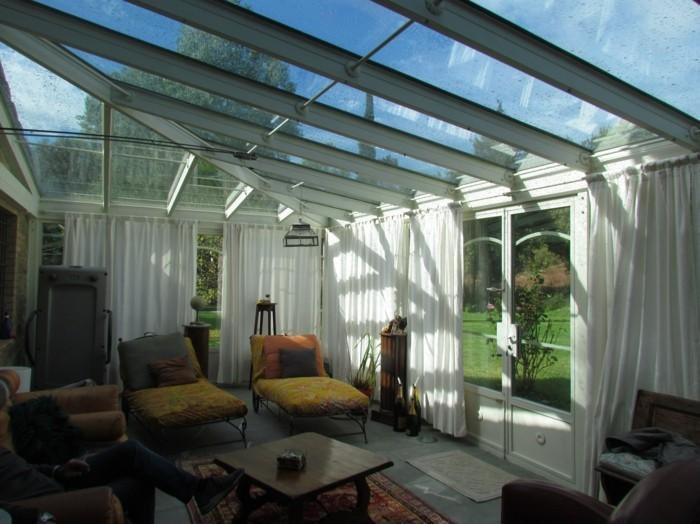 veranda-moderne-aménagée-avec-beaucoup-de-goût-pour-les-détails-rideaux-blancs-très-légers-qui-apportent-de-l-élégance-toit-veranda-vitrée