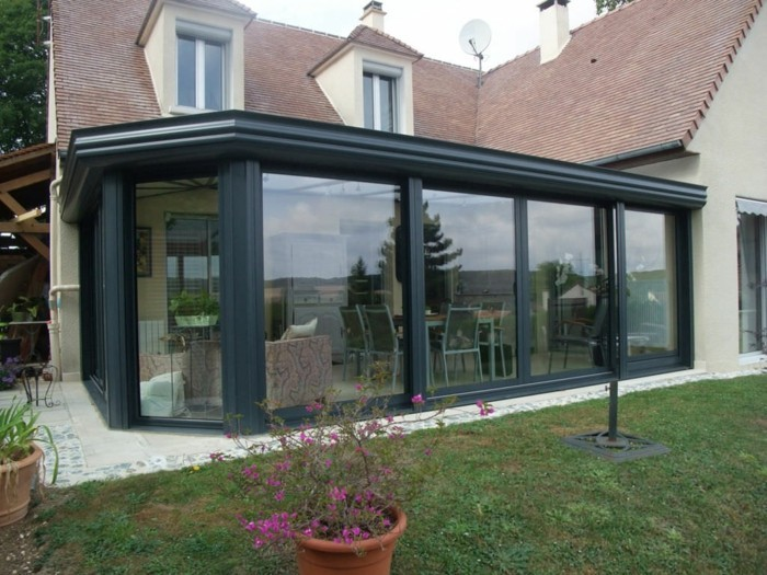 veranda-moderne-qui-ajoute-une-touche-moderne-à-cette-maison-de-style-classique-véranda-noire-en-aluminium-vitrages