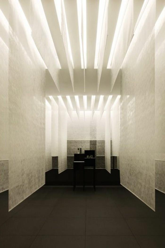 117-Luminaires couloir. Plancher noir. Murs et plafond blancs.