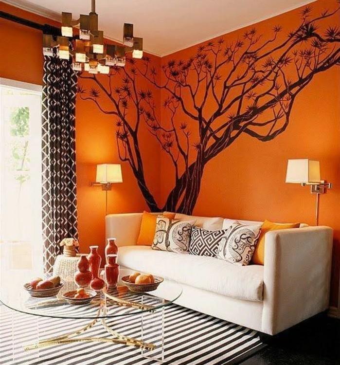couleur-peinture-salon-orange-avec-un-joli-sticker-mural-arbre-canape-blanc-casse-tapis-en-noir-et-blanc-table-a-cafe-en-verre-design-original