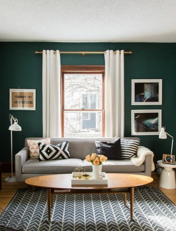 une-solution-tres-tendance-couleur-mur-salon-vert-émeraude-canape-gris-table-ovale-tres-sympa-tapis-en-noir-et-blanc