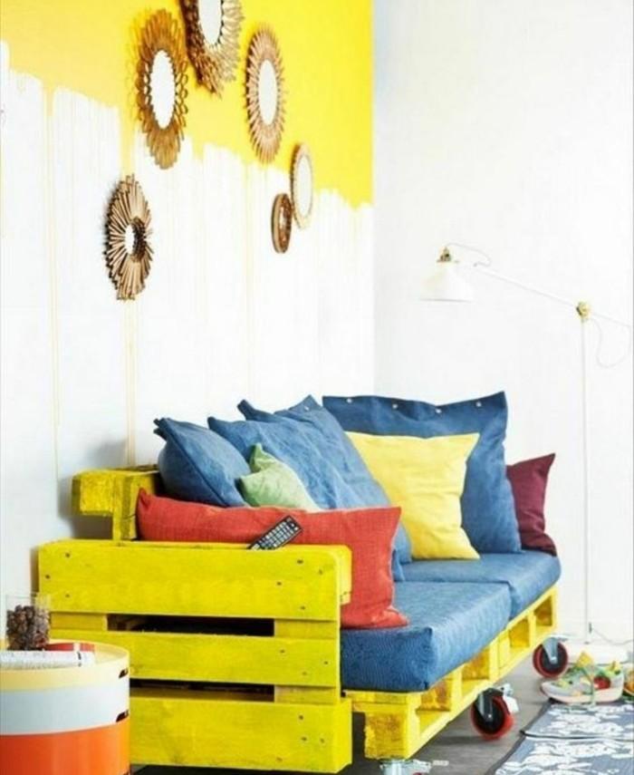 comment-fabriquer-un-canape-en-palette-superbe-idee-canape-a-rouolettes-jaune-assises-bleues-coussins-de-differentes-couleurs