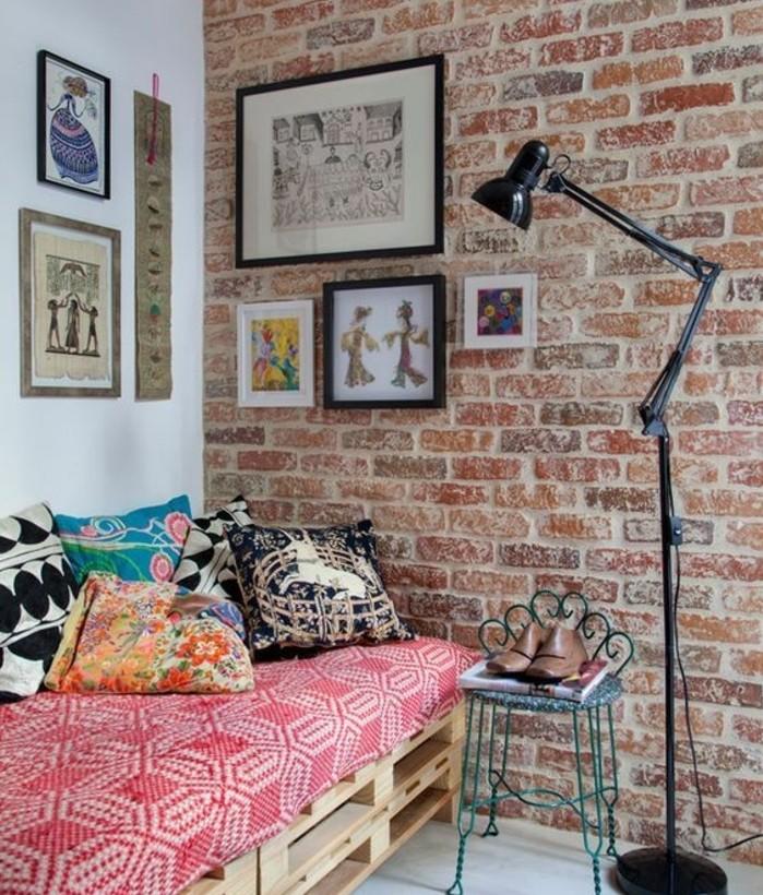 deco-tres-artistique-mur-en-briques-canape-en-palette-coussins-multicolores-ambiance-accueillante