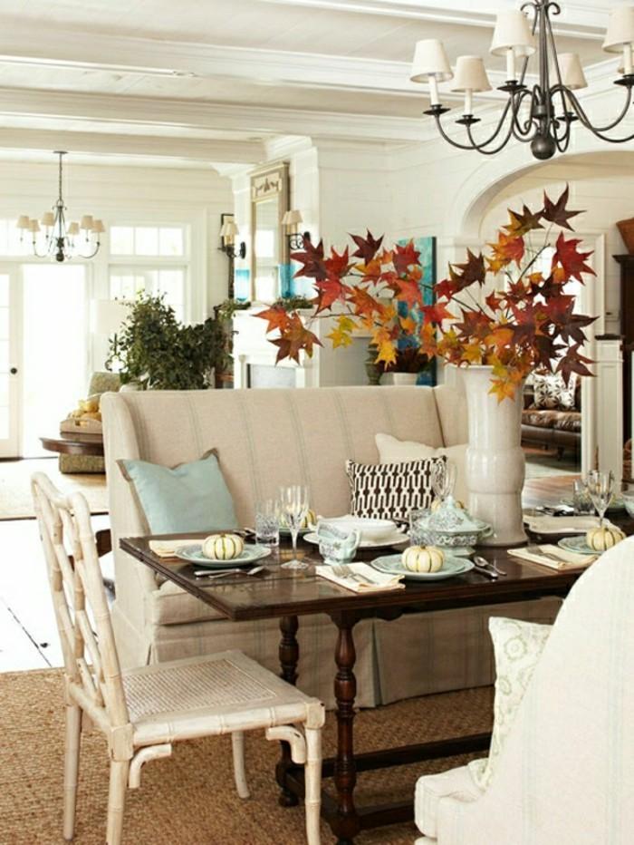 jolie-deco-de-table-en-bois-fonce-chaise-en-bois-blanc-canape-beige-vase-de-fleurs-oranges