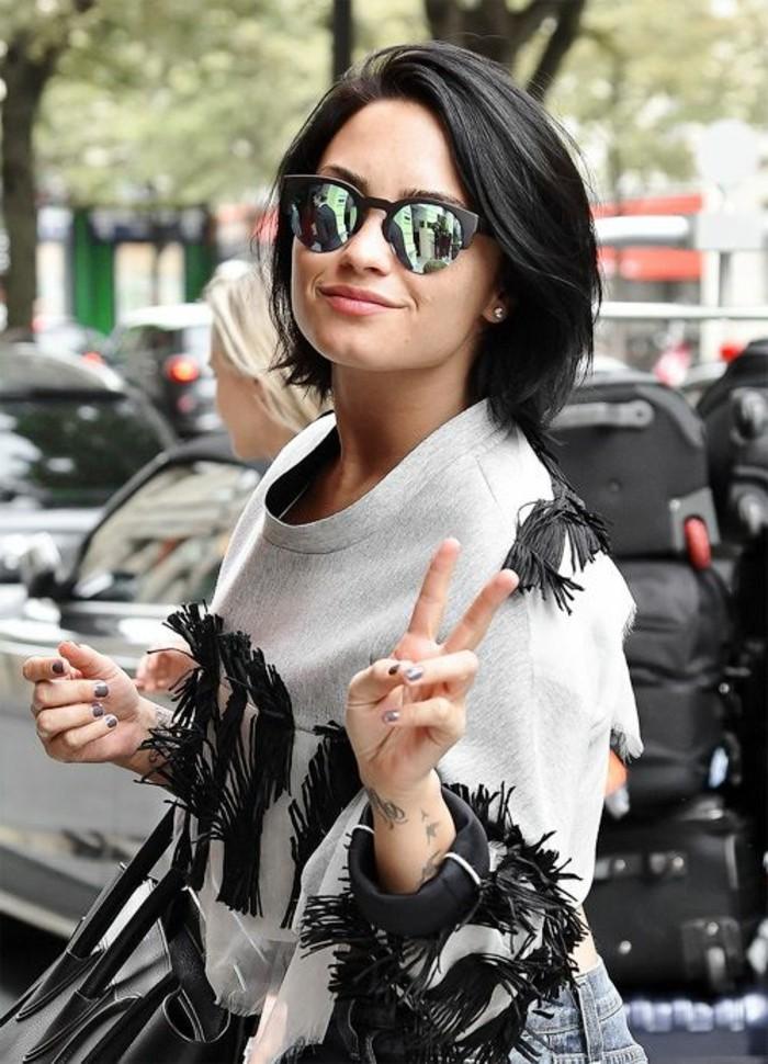 modele-coupe-courte-cheveux-noir-lunettes-de-soleil-refletant-blouse-gris