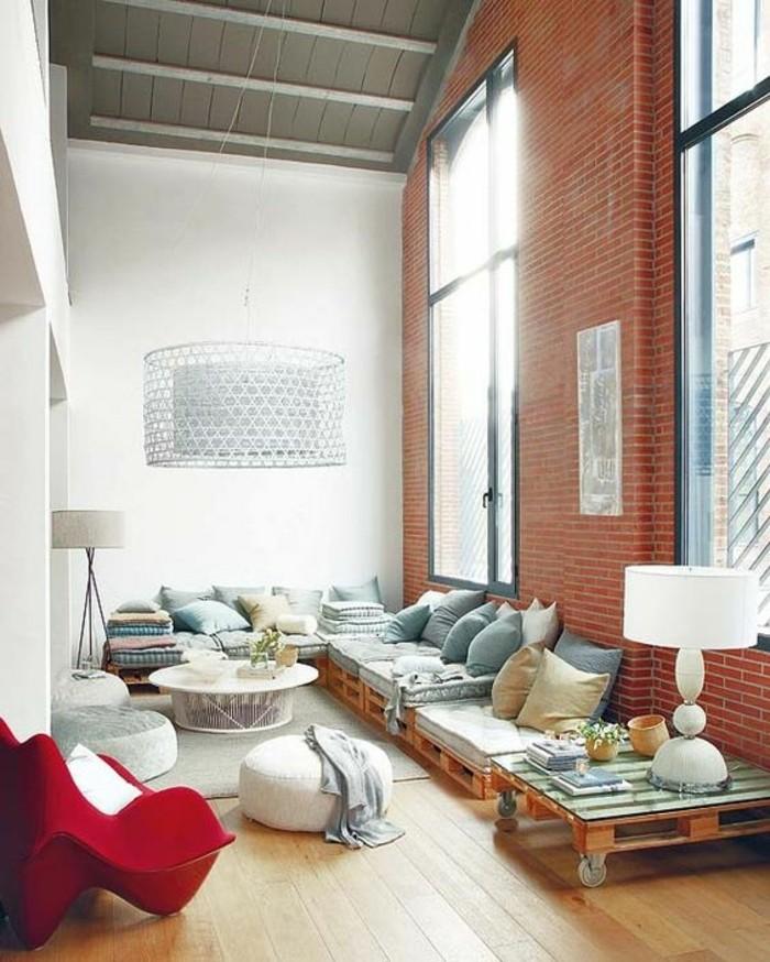 un-salon-look-chic-et-industriel-un-grand-canape-en-palette-petite-table-en-palette-a-roulettes-poufs-blancs
