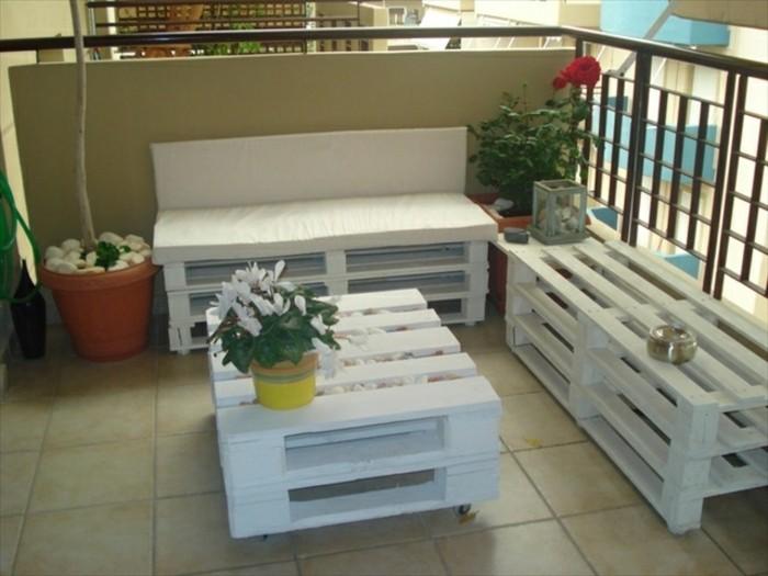 une-terrasse-amenagee-avec-des-meubles-en-palette-blancs-canape-palette-table-basse-blanche-a-roulettes