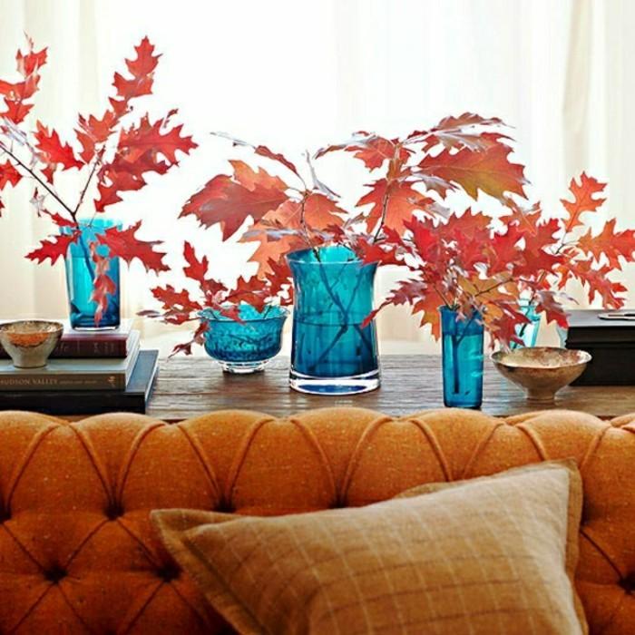 vase-en-verre-bleu-branches-ave-feuilles-oranges-canape-orange-dans-le-salon