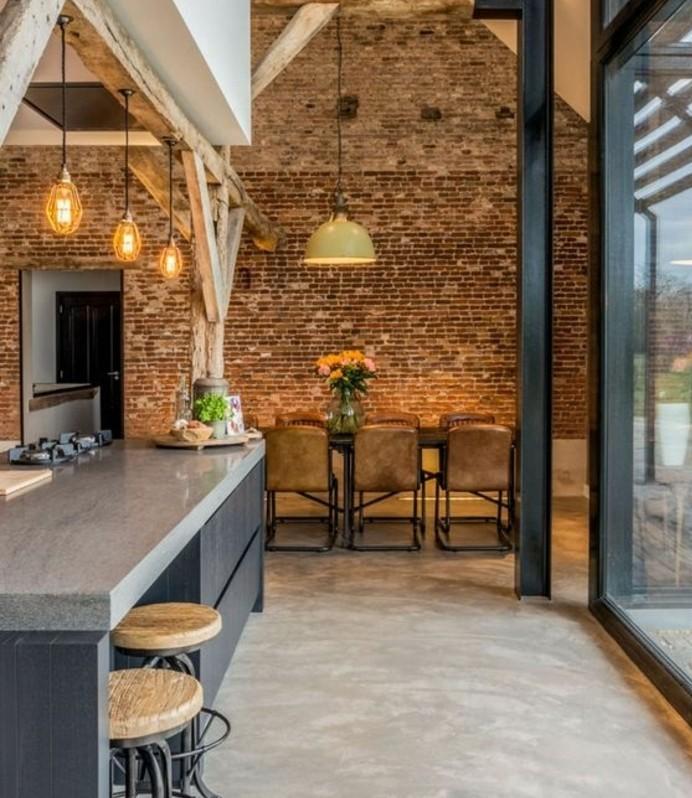 cuisine-loft-industriel-poutres-uses-mur-en-briques-coin-repas-acec-des-meubles-industriels-sol-en-beton-cire