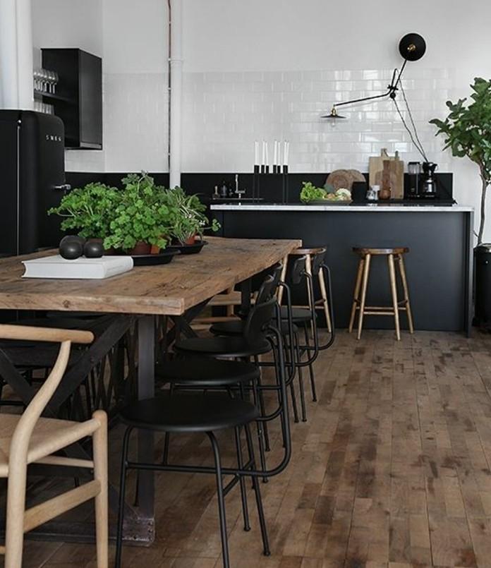 meuble-cuisine-et-tabourets-noirs-table-en-bois-brut-credence-en-carrelage-blanc-peinture-blanche-sol-en-bois