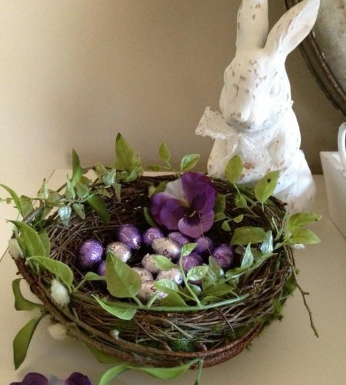 panier-tresse-decore-avec-de-la-vegetation-et-contenant-des-oeufs-de-chocolat-figurine-lapin-de-paques