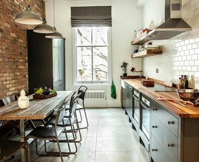 petite-cuisine-industrielle-tres-sympa-mur-en-briques-comme-point-focal-credence-en-carrelage-blanc-table-en-bois-chaises-industrielles-plan-de-travail-et-etageres-en-bois-facade-cuisine-grise