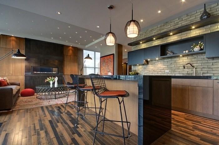 style-loft-et-industriel-pour-cette-cuisine-ultra-moderne-et-tres-chic-mur-en-briques-suspensions-industrielles-meubles-cuisine-et-ilot-de-cuisine-en-noir-et-bois-chaises-en-rouge-et-noir