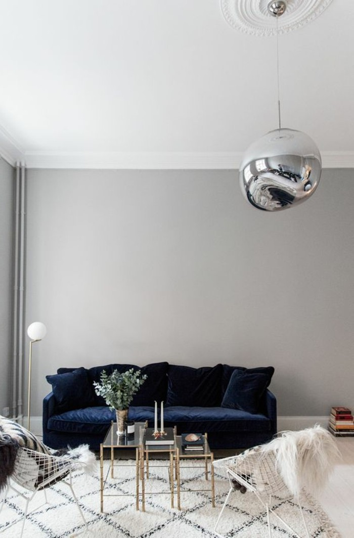 tapis-blanc-noir-canape-bleu-fonce-table-en-verre-et-metal-lustre-boule-mur-gris