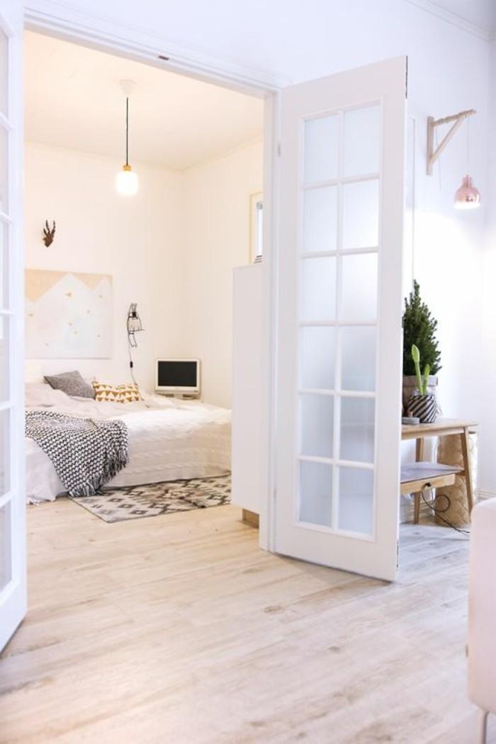 chambre-a-coucher-sol-en-parquet-clair-tapis-blanc-noir-mur-beige-blanc-idee-deco-interieur