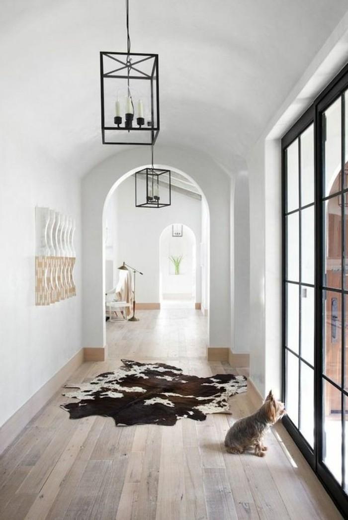 couloir-sol-en-bois-brut-clair-tapis-en-peau-d-animal-murs-blancs-fenetre-grande