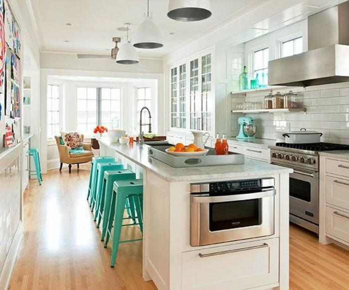 cuisine-equipee-avec-ilot-central-tabourets-tolix-bleus-plan-de-travail-blanc