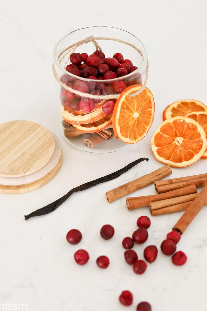 pot en verre rempli de canneberges séchées, tranches d orange et des batons de cannelle, fabriquer pot pourri, diy cadeau noel