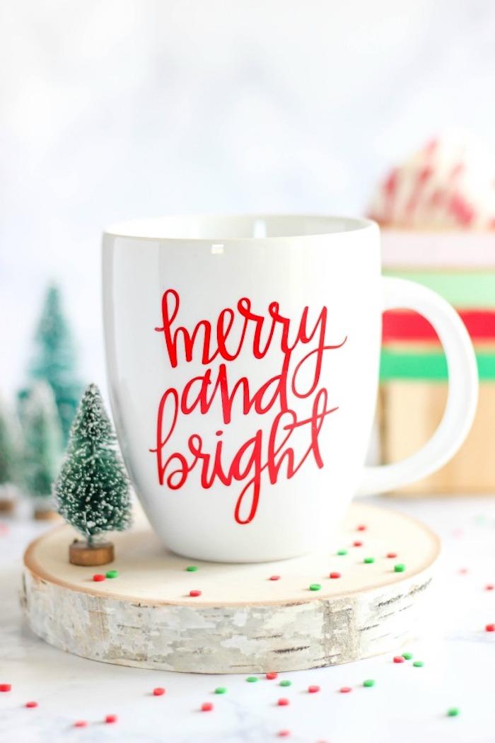tasse blanche customisée de lettres rouges texte joyeux noel sur rondin de bois à coté de figurine sapin, idée de cadeau pour noël