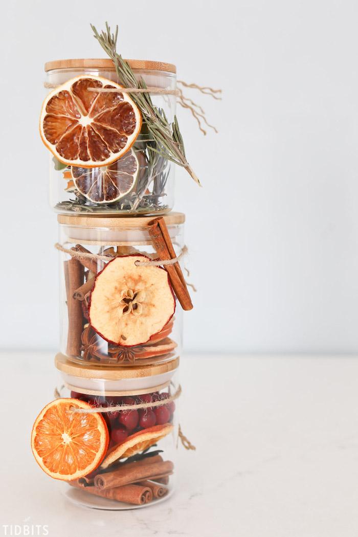 pot en verre pot pourri maison rempli de tranches de fruits séchés, batons de cannelle et autres ingredients de noel