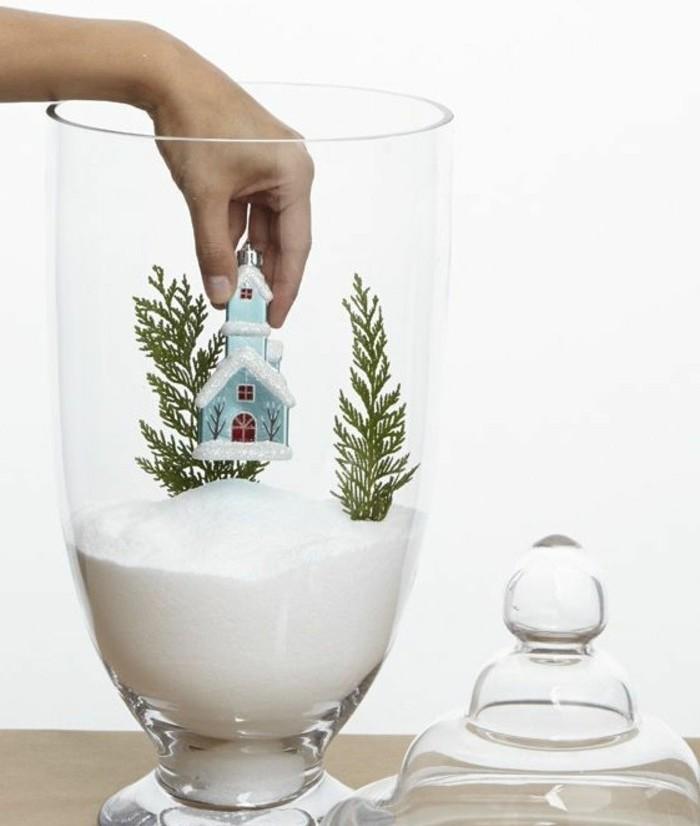 une-superbe-idee-de-decoration-de-noel-recipient-en-verre-plein-de-la-fausse-neige-branches-de-sapin-et-maison-enneige