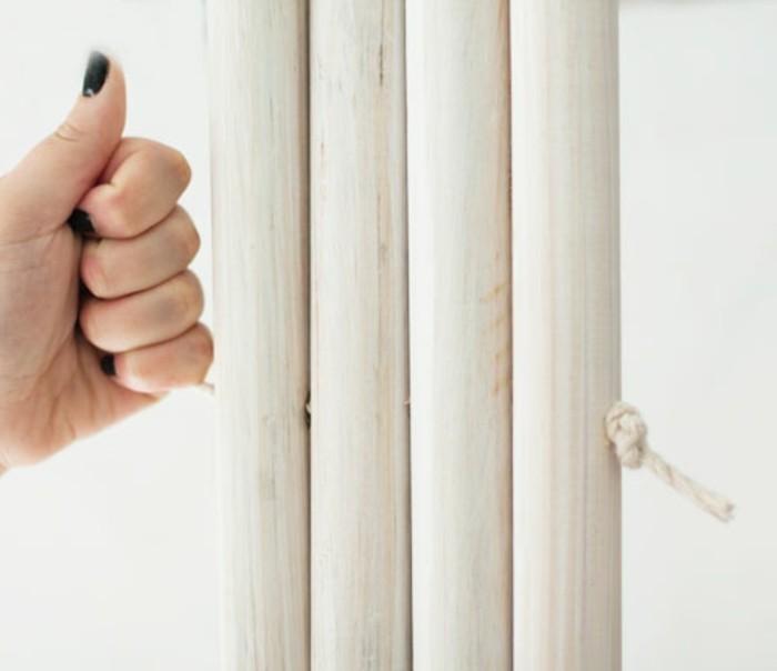 assembler-les-poteaux-en-bois-a-l-aide-de-la-corde-pour-fabriquer-un-tipi-armature-former-des-noeuds-aux-extremites