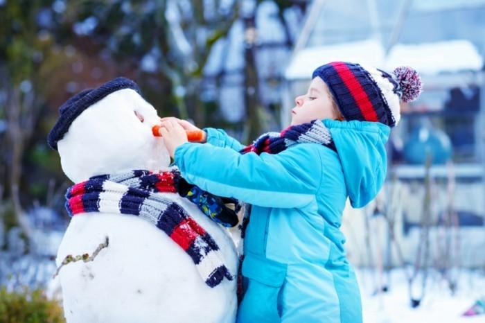 Funny kid boy making a snowman in winter