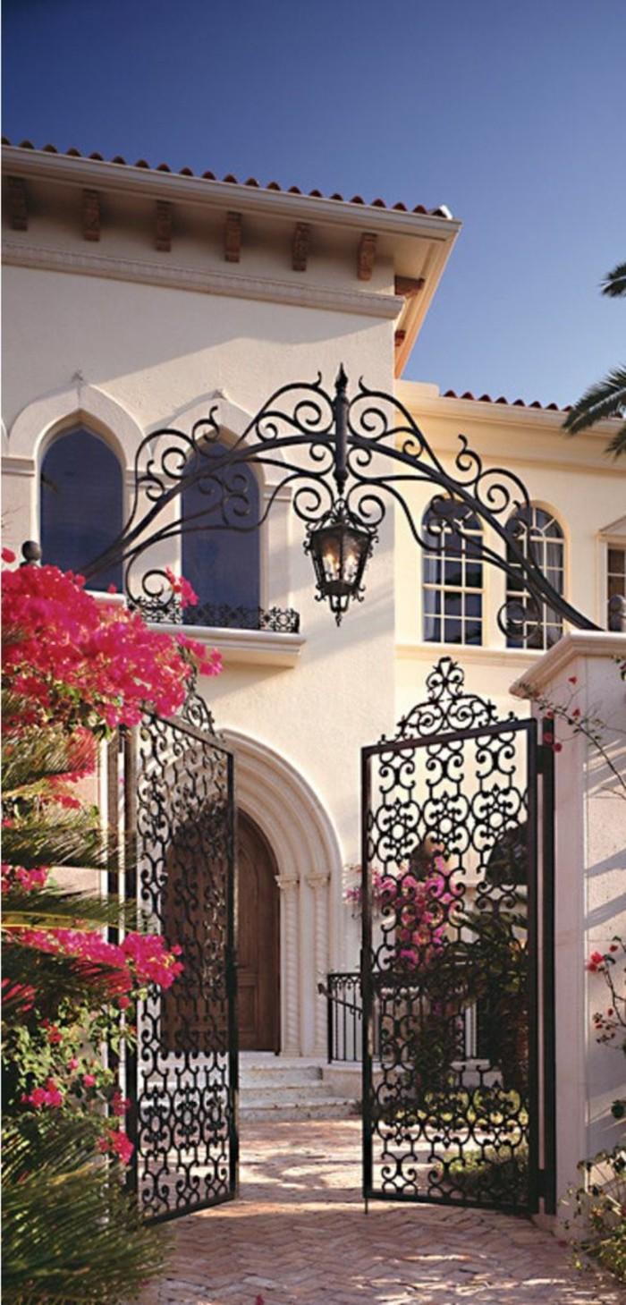 barriere-fer-forge-broussailles-roses-lanterne-pendante-maison-a-deux-etages