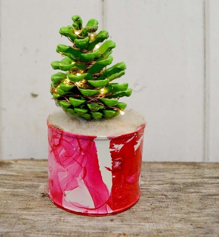 idée bricolage noel facile, modèle de mini sapin fait main en pomme de pin peinte en vert décoré de guirlande lumineuse