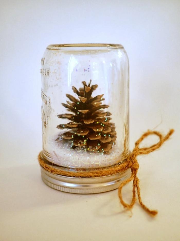 fabriquer une boule à neige soi-même, bocal en verre rempli de pomme de pin noel, objet de déco Noël facile à faire