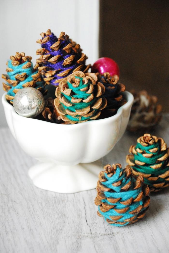idée bricolage pomme de pin maternelle, personnaliser des pommes de pin avec fil en laine, diy déco de Noël fait main
