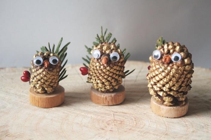 que faire avec des pommes de pin pour noel, diy hibou en pomme de pin dorée avec yeux mobiles et branche de sapin