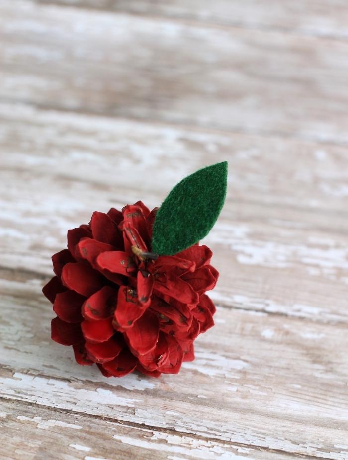fabriquer un objet décoration noel en pommes de pin peint en rouge avec feuille en feutrine, diy fruit en pomme de pin