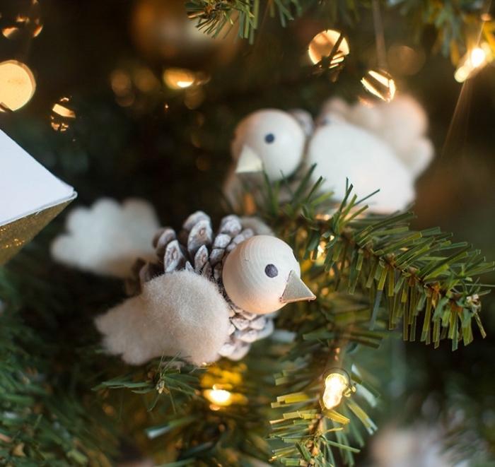 modèle d'ornement de sapin à faire soi-même, idée figurine oiseau en pomme de pin avec ailes en feutrine blanche