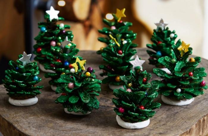 exemple bricolage de noel maternelle facile, modèle de mini sapin en pomme de pin peinte en vert et décoré avec perles