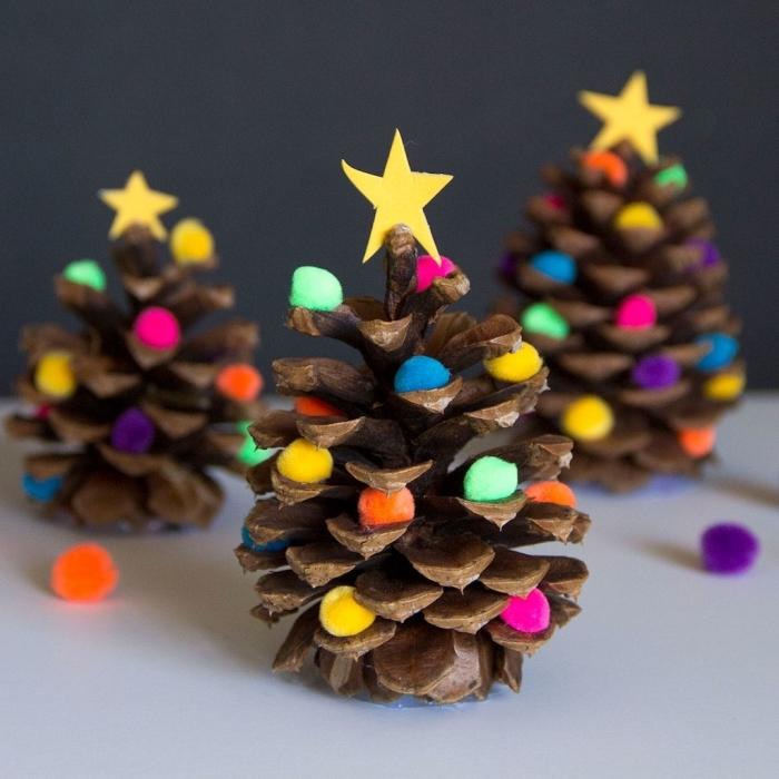 que faire avec des pommes de pin pour noel, modèles de mini sapins fait en pommes de pin décorés de pompons