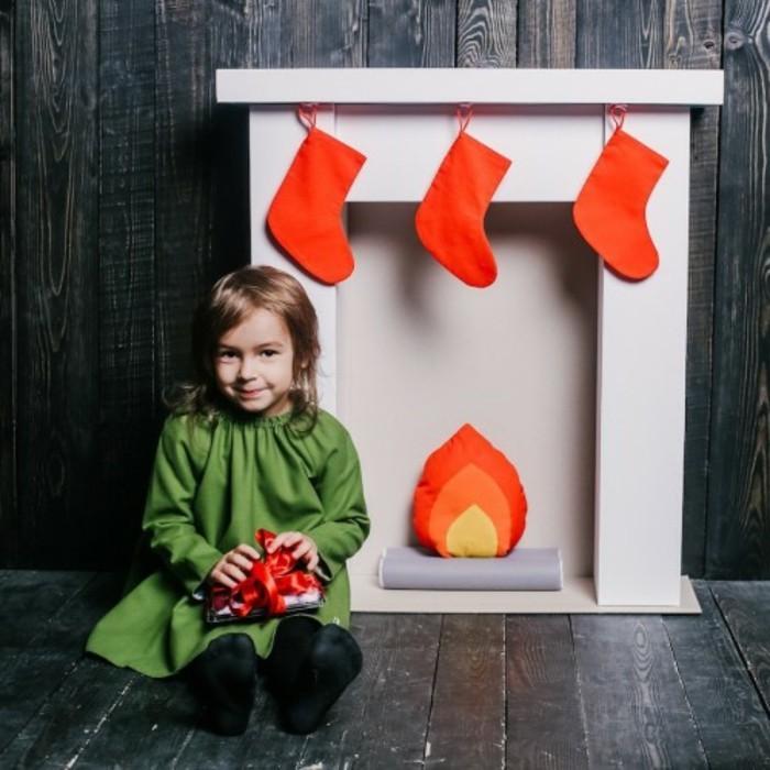 faire-une-cheminee-enfant-souriant-chaussettes-de-noel-feu