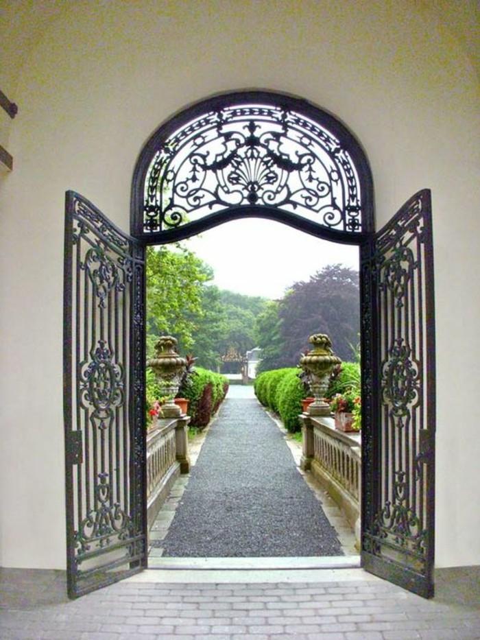 grille-fer-forge-sentier-magique-vue-vers-le-jardin-arbres-broussailles-porte-double
