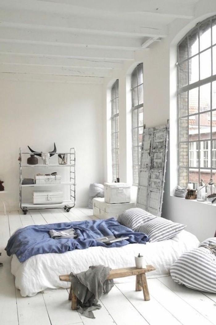 linge-de-lit-blanc-couverture-de-lit-bleu-fonce-sol-en-planchers-blancs-murs-blancs
