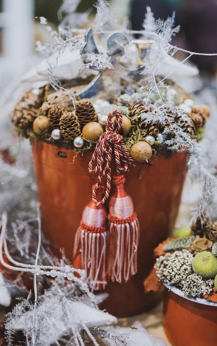 exemple de centre de table noel fait maison, réaliser une déco pour Noël avec pommes de pin et ornements de sapin