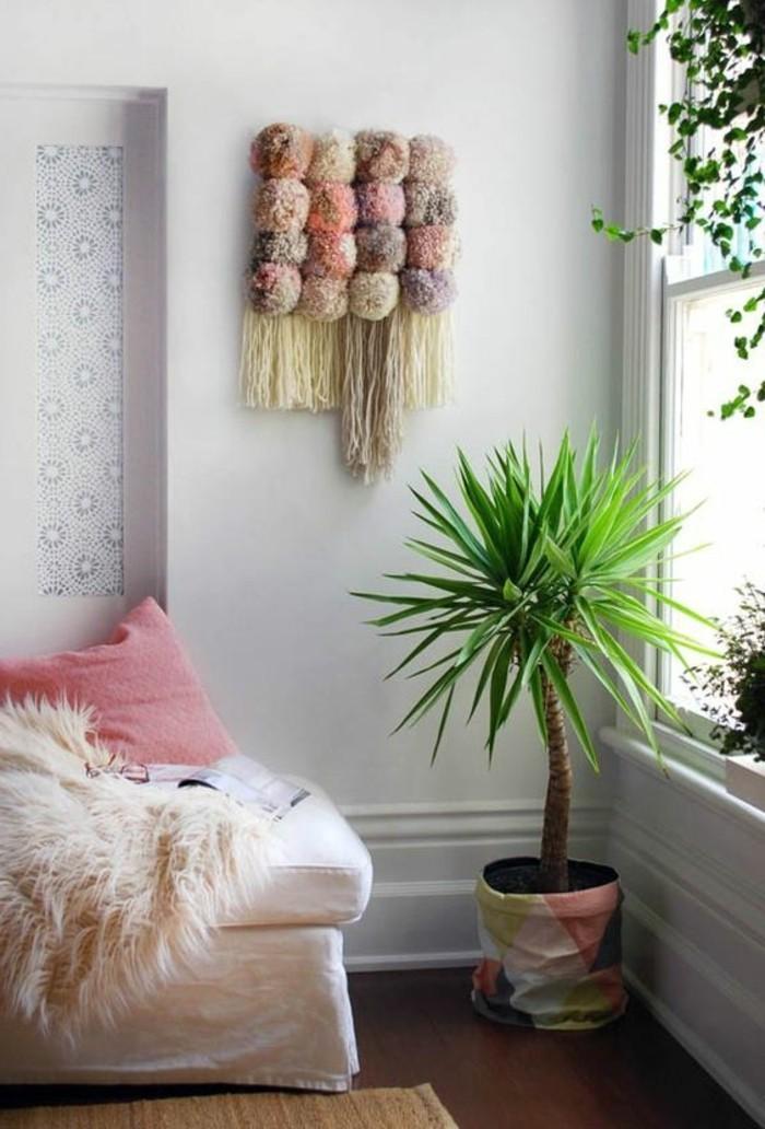 pompon-en-laine-palme-coussin-rose-parquet-de-bois-fonce