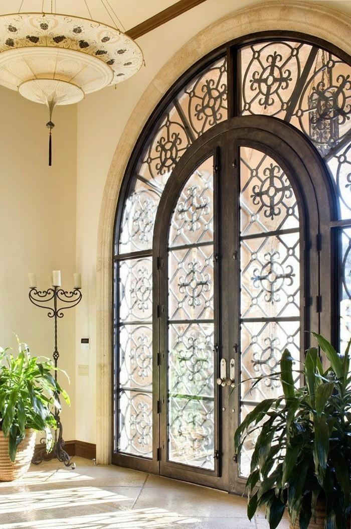 porte-en-fer-forge-chandelier-sur-pied-murs-en-blanc-porte-double-grande-plantes-vertes