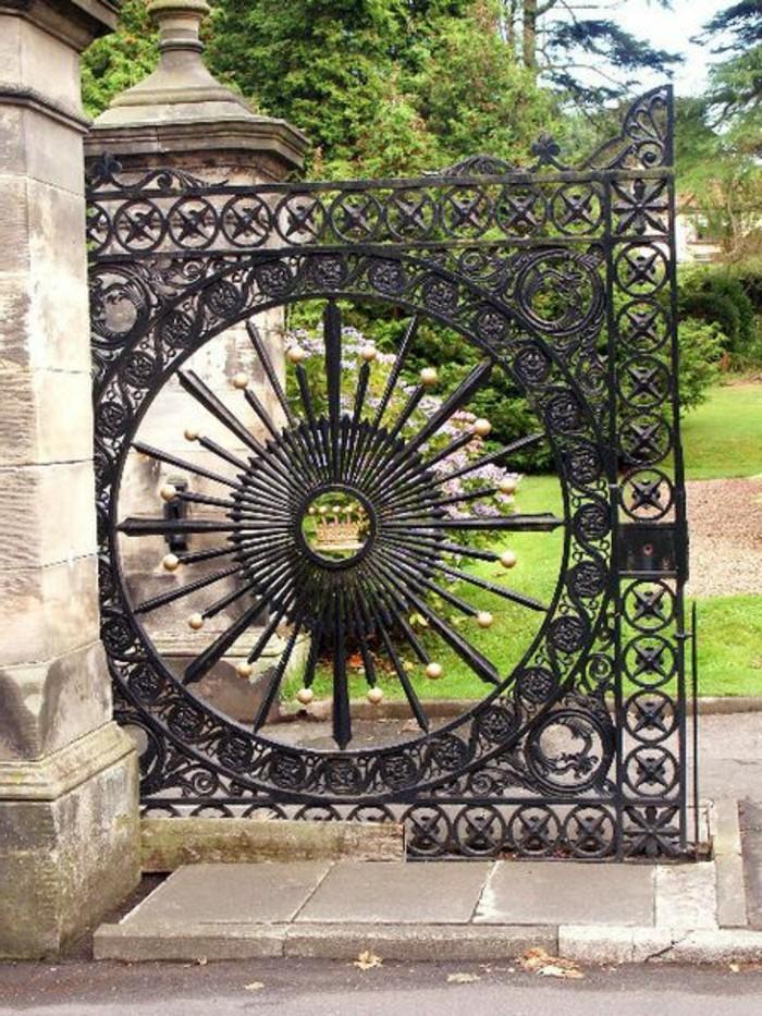porte-en-fer-forge-colonnes-massives-jardin-vert-broussailles-arbres-portails
